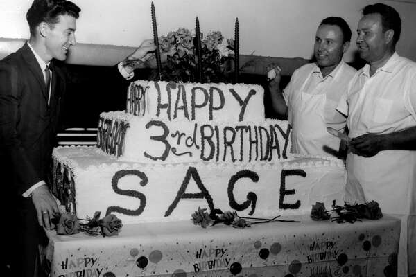 From the May 27, 1963, Chronicle: Sage Department Store, 8555 Gulf Freeway, Houston, Texas, is noting its third anniversary with a week-long celebration that began Monday. Sage is a membership store, but will be open to the public this week. Jerry Kalmin, left, store manager, is shown putting the third candle on the cake that will be served. Looking on are bakers T. Frank Ashcraft, center, and Tom Ashcraft. The three-tiered, 51-layer cake weighs more than 1000 pounds and is six feet square at its base.