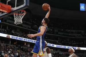 Golden State Warriors guard Klay Thompson, front, goes up for a basket past Denver Nuggets forward Paul Millsap in the first half of an NBA basketball game, Tuesday, Jan. 15, 2019, in Denver. (AP Photo/David Zalubowski)