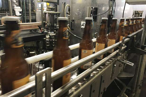 "In this Jan. 14, 2019, photo, bottles, freshly filled with beer, move on a belt at Lakefront Brewery in Milwaukee. The federal shutdown is impacting the federal agency Alcohol and Tobacco Tax and Trade Bureau, which approves licenses for new breweries, some ingredients and labels for beers sent out of state. The brewery is now waiting for the federal agency to approve the ""My Turn: Chuck"" beer label, so they can sell it out of state. (AP Photo/Carrie Antlfinger)"