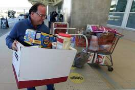 Erwin Guzman drops a food and supply donation for TAS workers at Orlando International Airport Wednesday, Jan. 16, 2019, in Orlando, Fla. as the partial government shutdown moves through its fourth week Wednesday, Jan. 16, 2019, in Orlando, Fla.