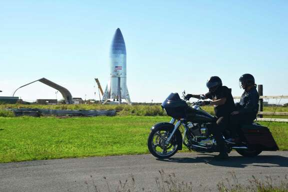 In this Saturday, Jan. 12, 2019 photo, a motorcyclist rides off in his Harley Davidson, across from SpaceX prototype Starship hopper at Boca Chica Beach, Texas. (Miguel Roberts/The Brownsville Herald via AP)