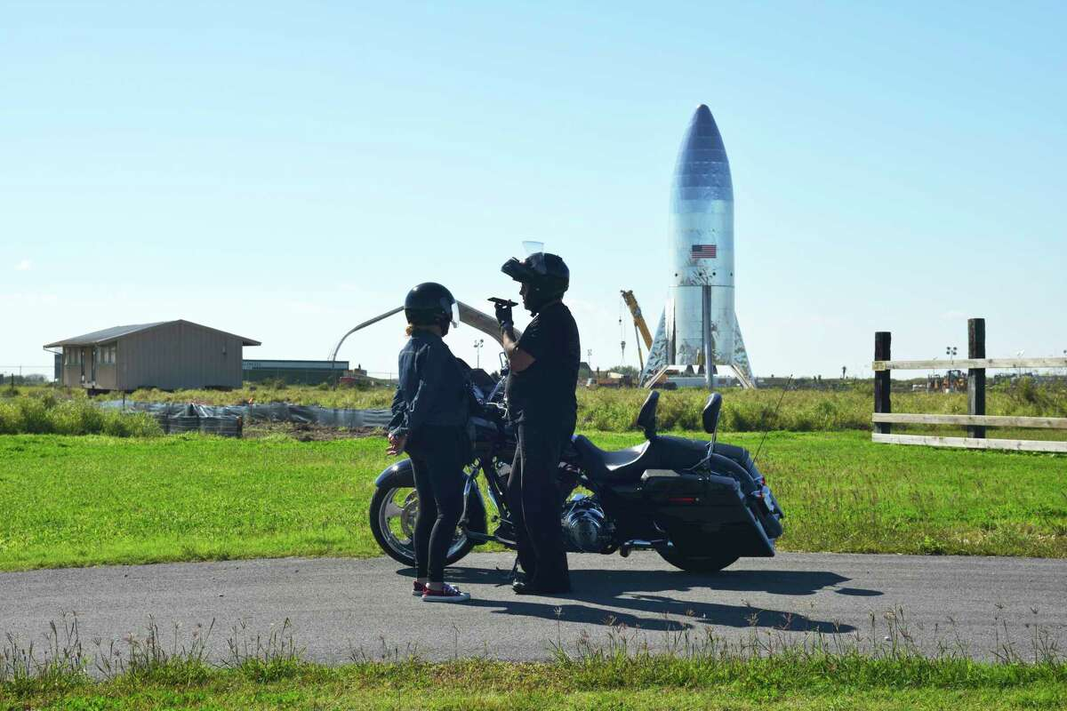 In this Saturday, Jan. 12, 2019 photo, a motorcycle rider and passenger stand next to their Harley Davidson across from SpaceX prototype Starship hopper at Boca Chica Beach, Texas. High winds have reportedly knocked over the prototype.