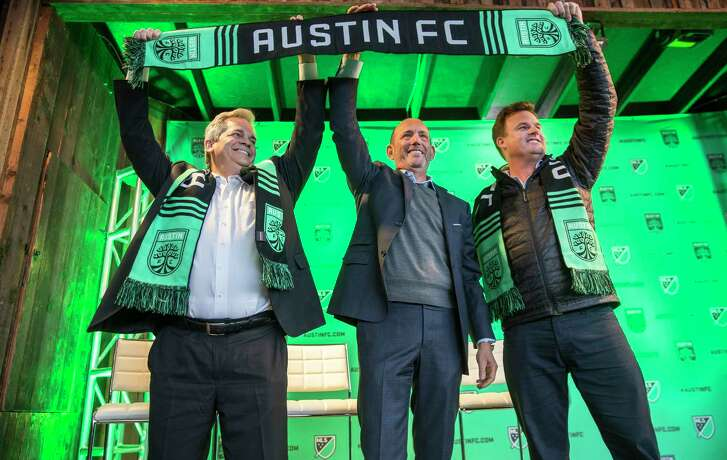 """Austin Mayor Steve Adler, Major League Soccer Commissioner Don Garber, and Anthony Precourt, majority owner of the team, from left, celebrate in downtown Austin, Texas, Tuesday, Jan. 15, 2019. The league formally welcomed Austin as its 27th franchise with a raucous downtown party full of chanting and flag-waving, and Garber calling the Texas capital a """"perfect fit."""" MLS said Austin will begin play in the 2021 season. (Ricardo B. Brazziell/Austin American-Statesman via AP)"""