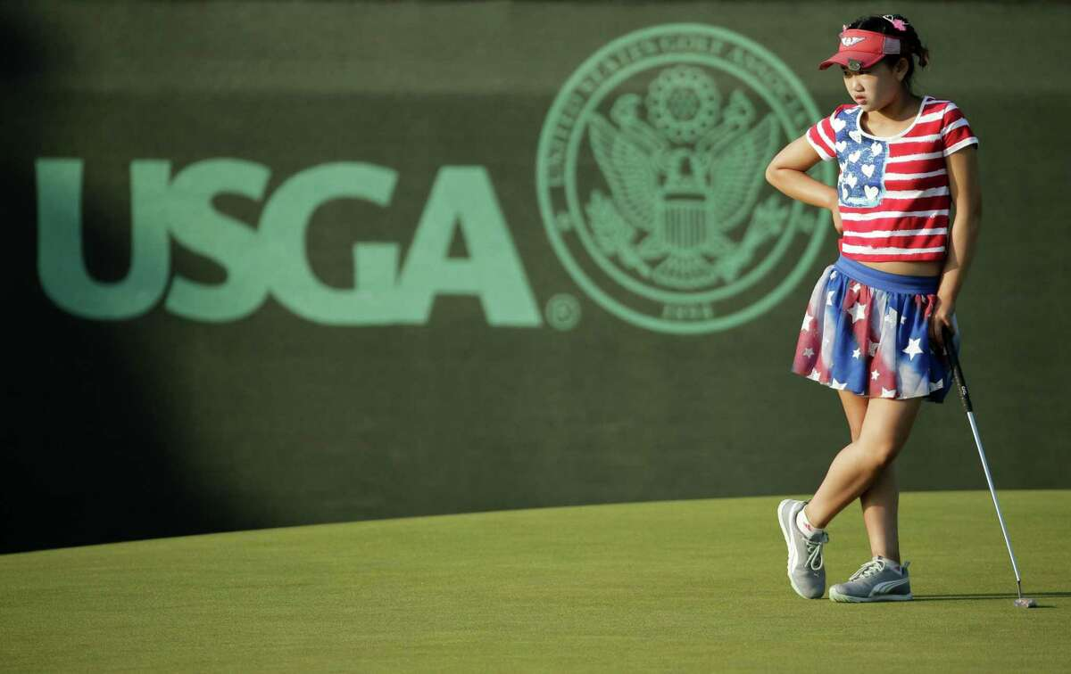 Eleven-year-old Lucy Li waits to putt on the 13th green during the first round of the U.S. Women's Open golf tournament in Pinehurst, N.C., in 2014.