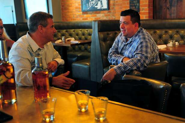 Eli's Tavern General Manager Kevin Fitzsimmons, right, chats with Proximo Spirits sales rep Ray Cruciani, at the restaurant on Daniel Street in Milford in 2015. On Wednesday, Eli's marked the 100th anniversary of Prohibition with happy hour speakeasy cocktails.