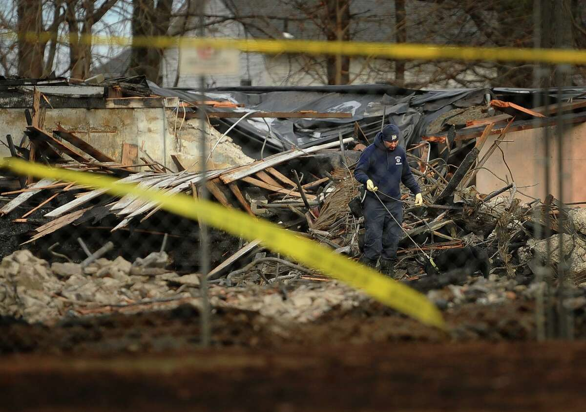 A dog sniffs through the burned wreckage during the ongoing fire investigation at the Shakespeare Theater site in Stratford, Conn. on Wednesday, January 16, 2019. The theater was destroyed by fire early Sunday morning.