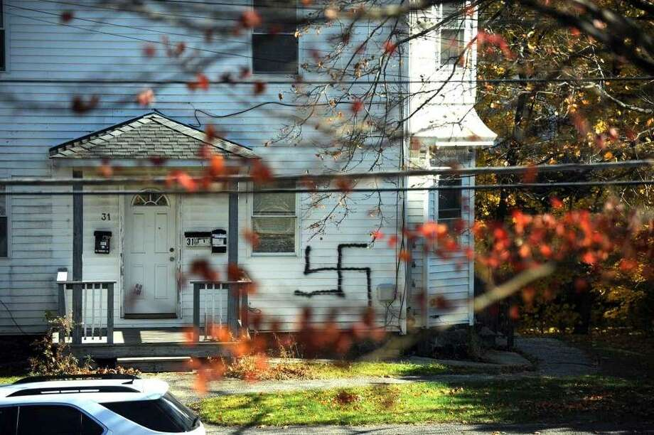 A swastika symbol was painted on a home and on a car on Division Street in Danbury in November, 2016. Photo: /