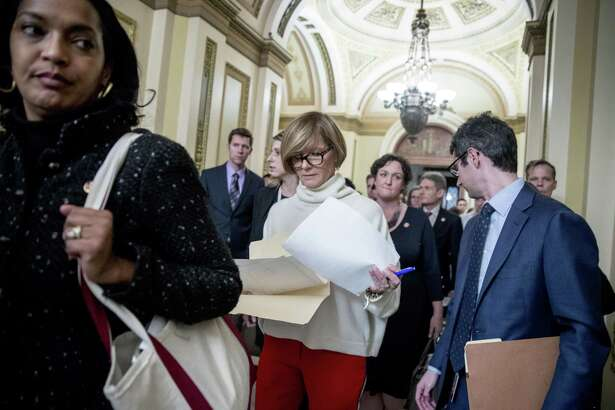 Rep. Susie Lee, D-Nev., center, carries a letter signed by a group of freshman Congressmen calling to an end to the government shutdown to deliver to the office of Senate Majority Leader Mitch McConnell of Ky., on Capitol Hill in Washington, Wednesday, Jan. 16, 2019. Also pictured is Rep. Jahana Hayes, D-Conn., left.