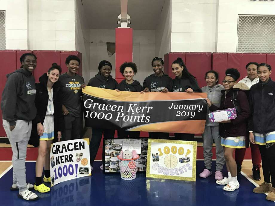 Kolbe Cathedral's Gracen Kerr with teammates after reaching the 1,000-point milestone on Tuesday in a 58-27 win over Brookfield. Photo: Submitted Photo
