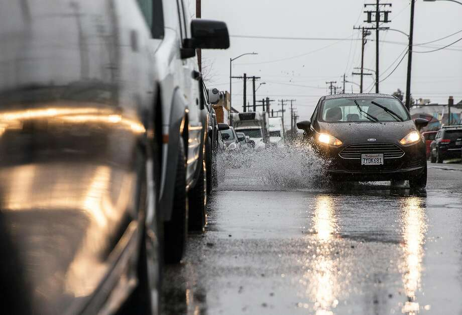 A car drives through floodwaters on Lowell Avenue during a heavy rain storm in Oakland, Calif. Wednesday, Jan. 16, 2019. Photo: Jessica Christian / The Chronicle