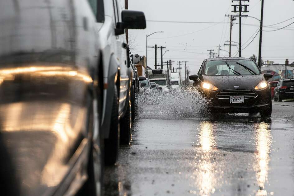 A car drives through floodwaters on Lowell Avenue during a heavy rain storm in Oakland, Calif. Wednesday, Jan. 16, 2019.