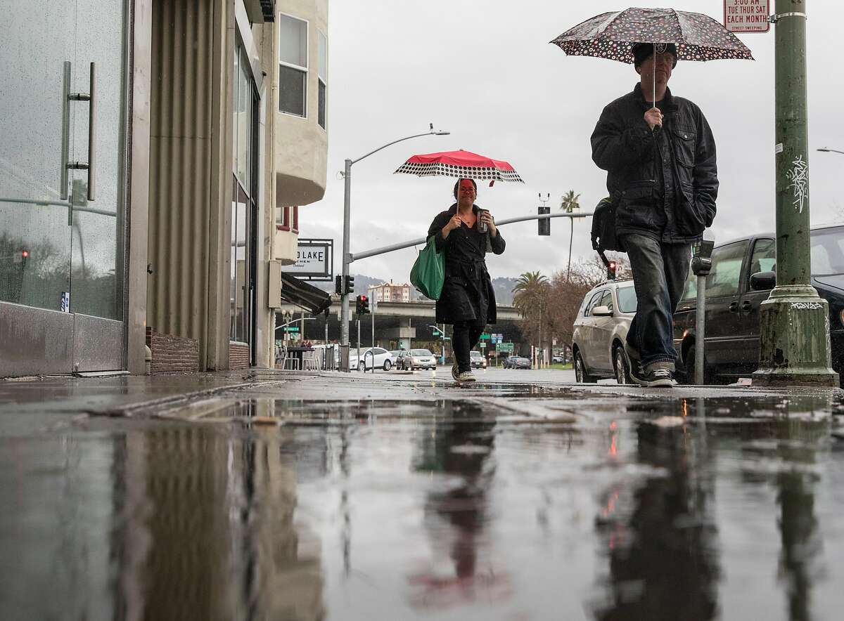 Pedestrians with umbrellas walk through a flooded sidewalk along Grand Avenue during a heavy rain storm in Oakland, Calif. Wednesday, Jan. 16, 2019.
