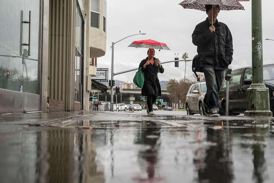 Pedestrians with umbrellas walk through a flooded sidewalk along Grand Avenue during a heavy rain storm in Oakland, Calif. Wednesday, Jan. 16, 2019.
