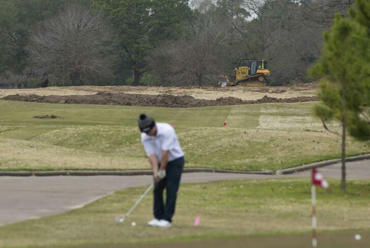 A golfer concentrates on his chipping game despite bulldozing efforts in the background helping to renovate Memorial Park Golf Course in preparation for the 2020 Houston Open.