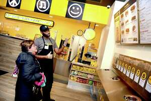 Ann Cohen DePalma (left) is assisted by shift leader Michael Stevenson with the ordering process at the new Which Wich on College St. in New Haven on January 16, 2019.