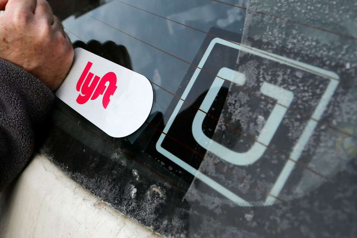 In this Jan. 31, 2018, file photo, a Lyft logo is installed on a Lyft driver's car next to an Uber sticker in Pittsburgh. The