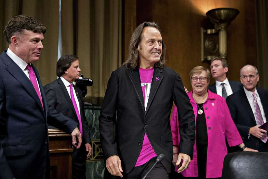 John Legere, chief executive officer of T-Mobile US Inc. (center) arrives at a Senate hearing in Washington, D.C., on June 27, 2018. Photo: Bloomberg Photo By Andrew Harrer. / © 2018 Bloomberg Finance LP