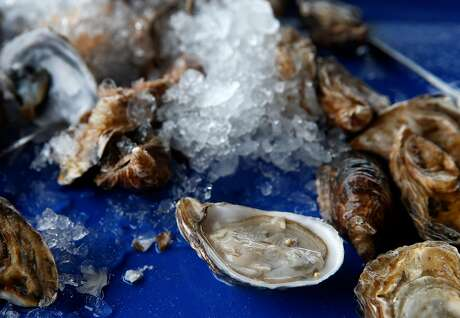 Raw oysters shipped in from Washington state are shucked by diners at Hog Island Oyster Farm in Marshall, Calif. on Wednesday, Jan. 16, 2019. Harvesting on Tomales Bay has been temporarily suspended following reports of a few customers becoming infected with norovirus after consuming the oysters.