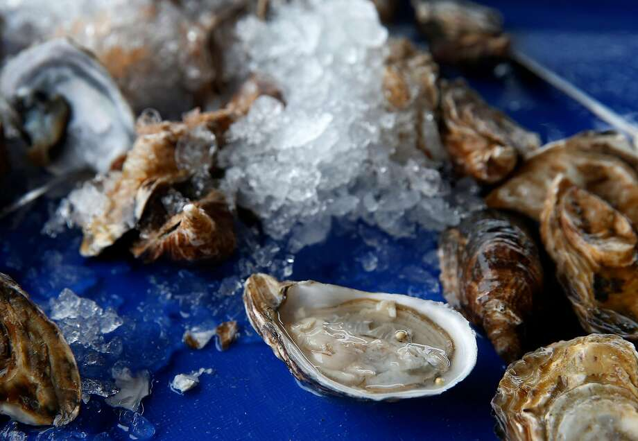 Raw oysters shipped in from Washington state are shucked by diners at Hog Island Oyster Co. in Marshall. Photo: Paul Chinn / The Chronicle