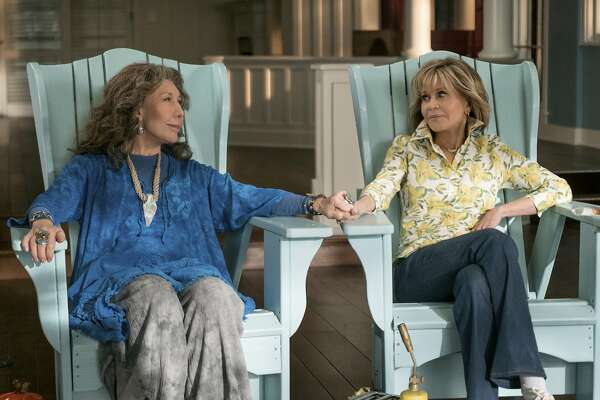 """This image released by Netflix shows Lily Tomlin, left, and Jane Fonda in a scene from the comedy series """"Grace And Frankie."""" As the fifth-season adventures of """"Grace and Frankie"""" begin, viewers can rest assured there's more to come. Series creator Marta Kauffman and Netflix said Tuesday, Jan. 15, 2019, that the comedy starring Fonda and Tomlin has been renewed for season six, due in 2020. (Ali Goldstein/Netflix via AP)"""
