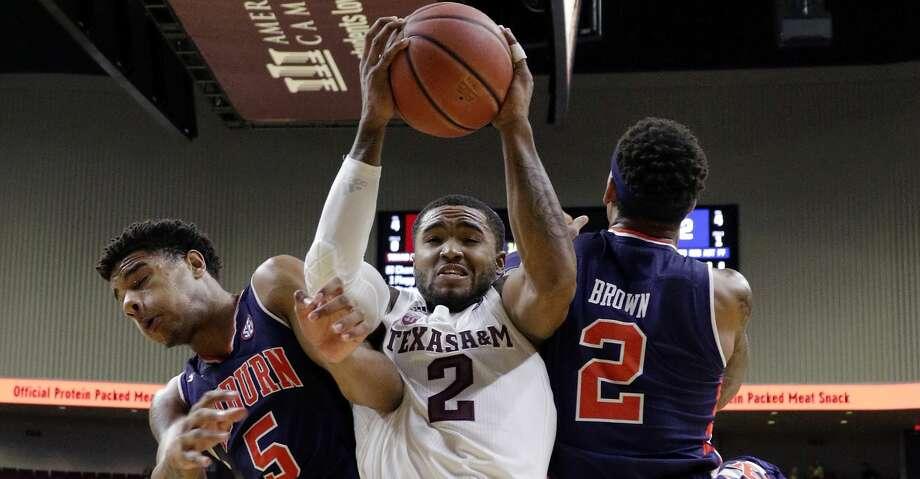 Texas A&M guard TJ Starks (2) is defended on a rebound between Auburn forward Chuma Okeke (5) and guard Bryce Brown (2) during the first half of an NCAA college basketball game, Wednesday, Jan. 16, 2019, in College Station, Texas. (AP Photo/Michael Wyke) Photo: Michael Wyke/Associated Press