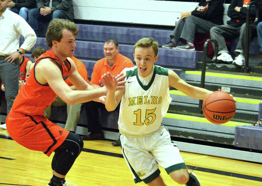 Metro-East Lutheran senior Jonah Wilson, right, drives to the basket during the first quarter of Wednesday's game against Hillsboro in the Rick McGraw Memorial Invitational at Litchfield High School. Photo: Scott Marion/Intelligencer