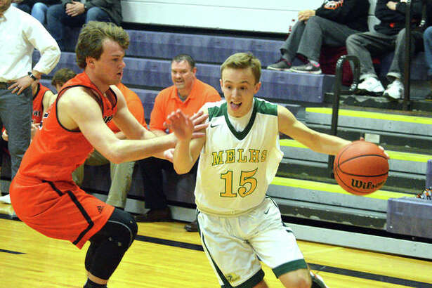 Metro-East Lutheran senior Jonah Wilson, right, drives to the basket during the first quarter of Wednesday's game against Hillsboro in the Rick McGraw Memorial Invitational at Litchfield High School.