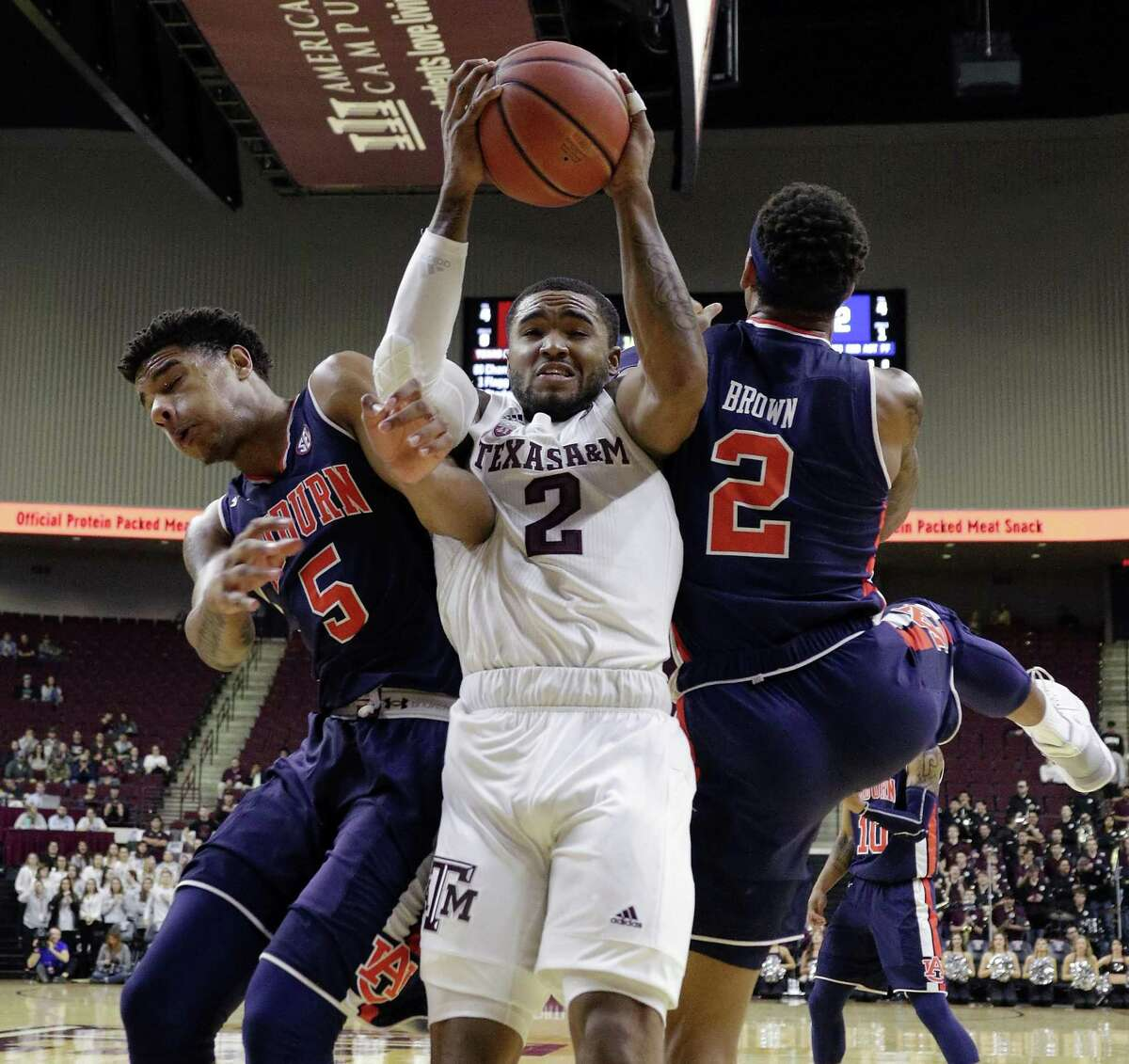 Texas A&M's TJ Starks (2) gets caught in a squeeze play between Auburn's Chuma Okeke, left, and Bryce Brown.