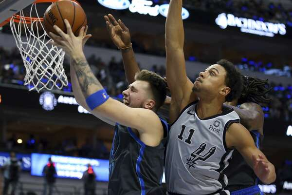 Dallas Mavericks forward Luka Doncic (77) pulls down a rebound against San Antonio Spurs guard Bryn Forbes (11) in the first half of an NBA basketball game, Wednesday, Jan. 16, 2019, in Dallas. (AP Photo/Richard W. Rodriguez)