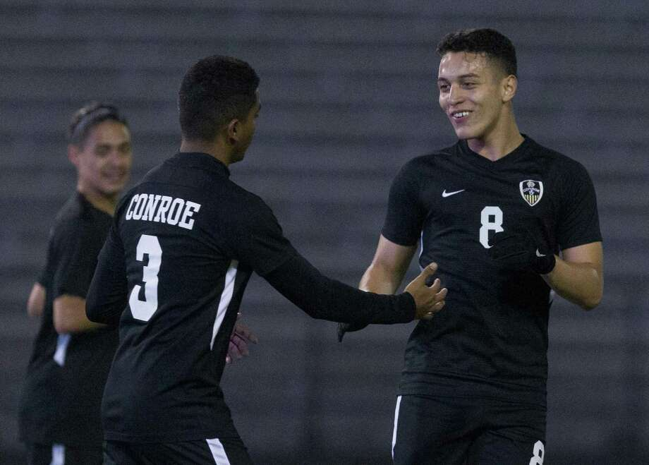 Josue Fuentes #8 of Conroe give a high-five to Misael Martinez after Martinez' goal during the first period of a non-district high school soccer match at Buddy Moorhead Stadium, Wednesday, Jan. 16, 2019, in Conroe. Photo: Jason Fochtman, Houston Chronicle / Staff Photographer / © 2019 Houston Chronicle