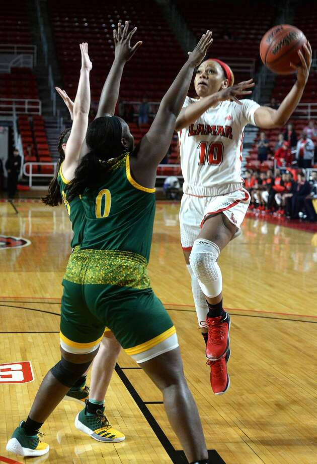 Lamar's Chastadie Barrs outs up her shot over Southeast Louisiana's Jaclyn Scholvin and Kyla Williams during their game Wednesday night at the Montagne Center. Photo taken Wednesday, January 16, 2019 Photo by Kim Brent/The Enterprise Photo: Kim Brent/The Enterprise