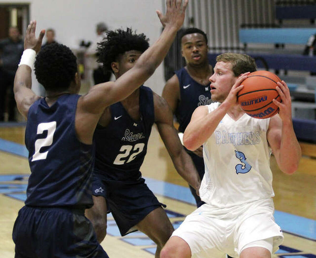 Jersey's Kurt Hall (right) looks for help out of a trap by McCluer North defenders during a Dec. 3 game at Havens Gym in Jerseyville. Hall and his teammates lost to Collinsville Wednesday in the Panther Classic.