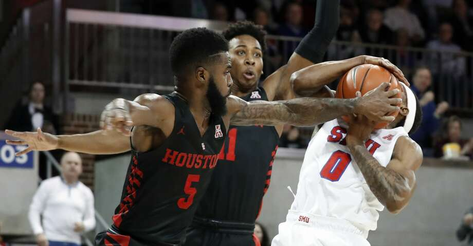 SMU guard Jahmal McMurray (0) is fouled by Houston guard Corey Davis Jr. (5) going up for a shot as Houston's Nate Hinton (11) helps defend beneath the basket in the first half of an NCAA college basketball game, Wednesday, Jan. 16, 2019, in Dallas. (AP Photo/Tony Gutierrez) Photo: Tony Gutierrez/Associated Press