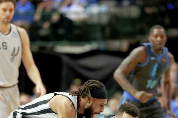 Patty Mills beats Dallas rookie Jalen Brunson to a loose ball. Mills hit 4 of 10 3-point attempts and finished with 14 points off the bench.