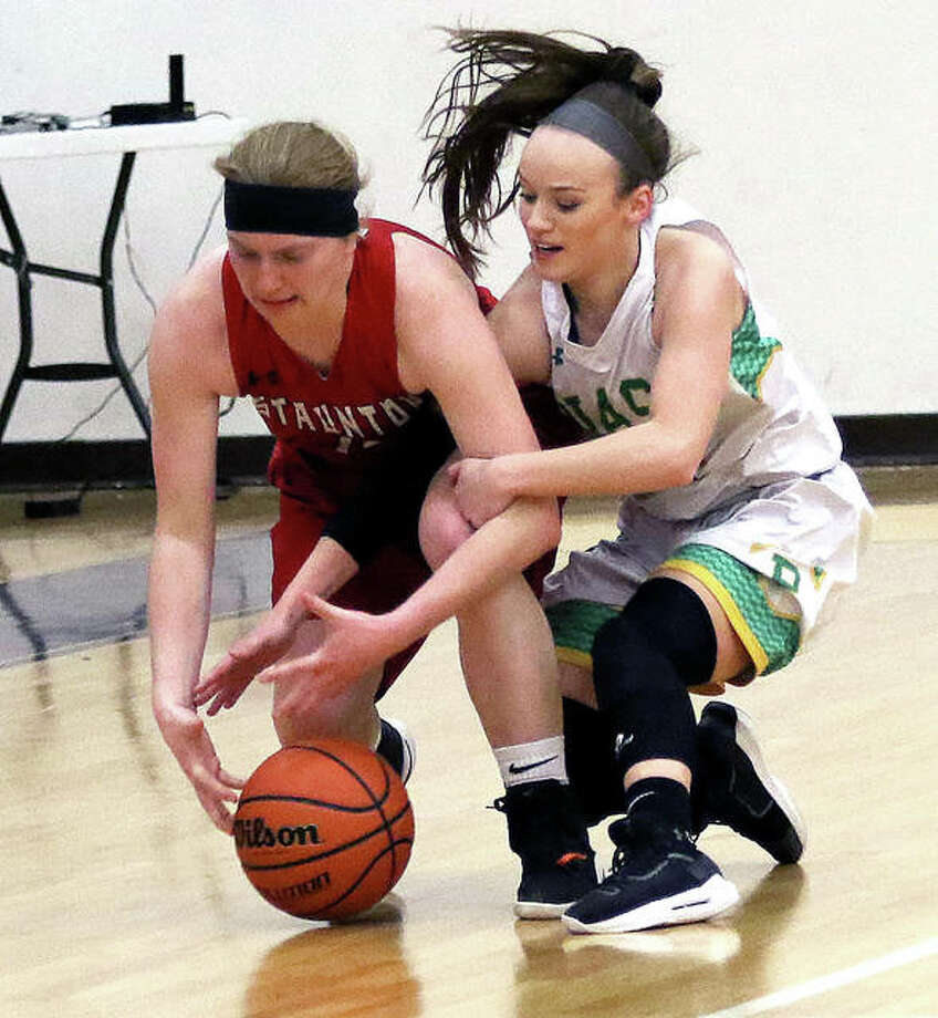 Staunton's Rebecca Caldieraro (left) and Southwestern's Abbey Burns battle for a loose ball in the second half of Wednesday night's semifinal at the Macoupin County Tournament in Mount Olive. Photo: Greg Shashack | The Telegraph