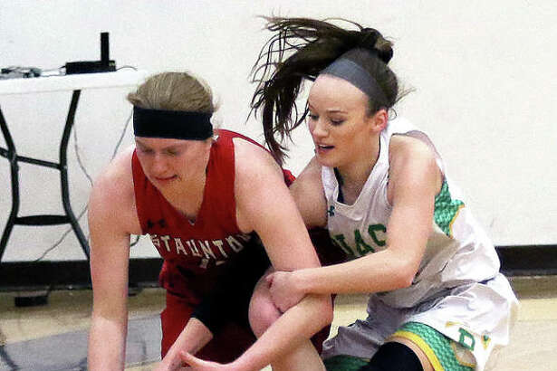 Staunton's Rebecca Caldieraro (left) and Southwestern's Abbey Burns battle for a loose ball in the second half of Wednesday night's semifinal at the Macoupin County Tournament in Mount Olive.