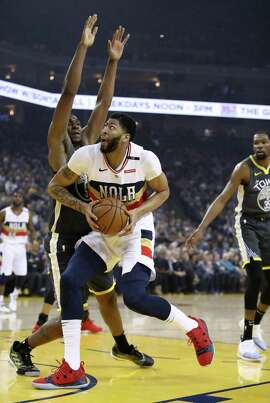 OAKLAND, CALIFORNIA - JANUARY 16: Anthony Davis #23 of the New Orleans Pelicans drives on Kevon Looney #5 of the Golden State Warriors at ORACLE Arena on January 16, 2019 in Oakland, California. NOTE TO USER: User expressly acknowledges and agrees that, by downloading and or using this photograph, User is consenting to the terms and conditions of the Getty Images License Agreement. (Photo by Ezra Shaw/Getty Images)