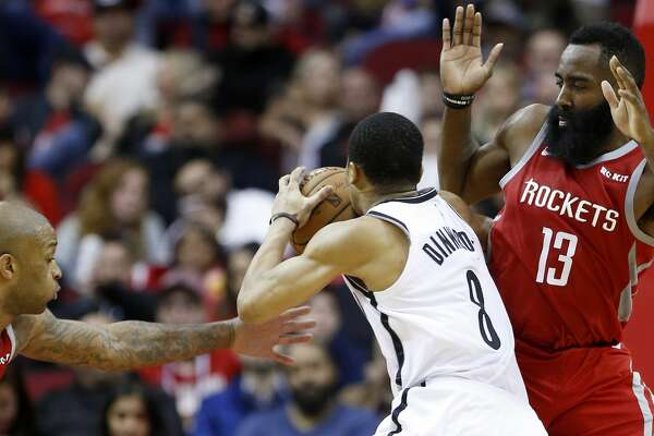 Brooklyn Nets guard Spencer Dinwiddie (8) drives to the basket between Houston Rockets forward PJ Tucker (17) and guard James Harden (13) during the second half of an NBA basketball game at Toyota Center on Wednesday, Jan. 16, 2019, in Houston.