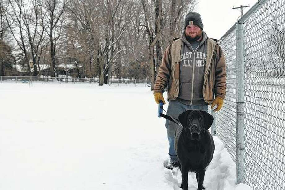 Tyler Stout of Jacksonville takes Gunner out for a walk in the snow-covered Jacksonville Bark Park on a chilly Wednesday.