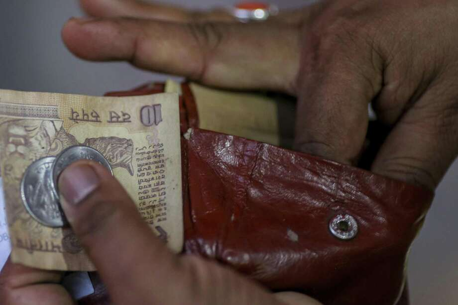 A man takes an 10-rupee banknote and one-rupee coins from a wallet on June 28, 2018, in Mumbai. Photo: Bloomberg Photo By Dhiraj Singh / Bloomberg