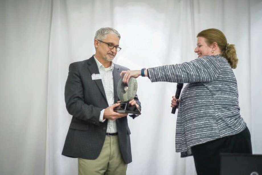 'Dave Kell, left, accepts the Leadership Midland Alumni Association's 'Leader of the Year' award from former recipient Wendy Kanar this week at The H Hotel.' (Ben Tierney/For the Daily News)
