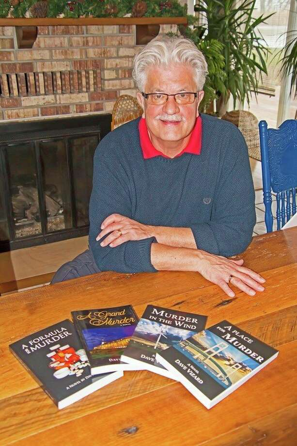 Author Dave Vizard is pictured in his home, with copies of each of his self-published novels. (Bill Diller/For the Tribune)