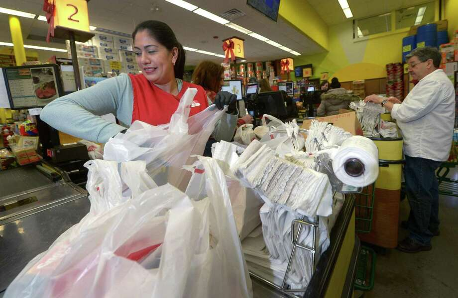 Cashier Beatriz Jimenez bags groceries at CTown last week in Norwalk. Photo: Erik Trautmann / Hearst Connecticut Media / Norwalk Hour