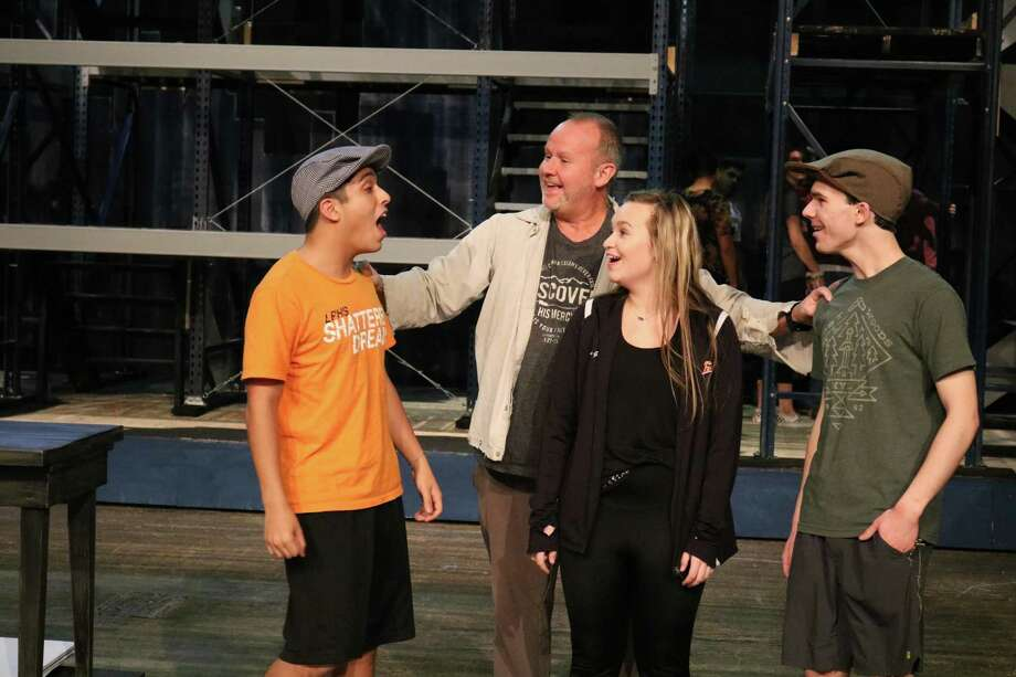 """La Porte High School students, from left, Adrian Escareno, Zoe Gibson and Luke Boriskie, rehearse a scene from Disney's """"Newsies the Musical"""" with the help of Jay Watson, one of the associate directors of the production."""