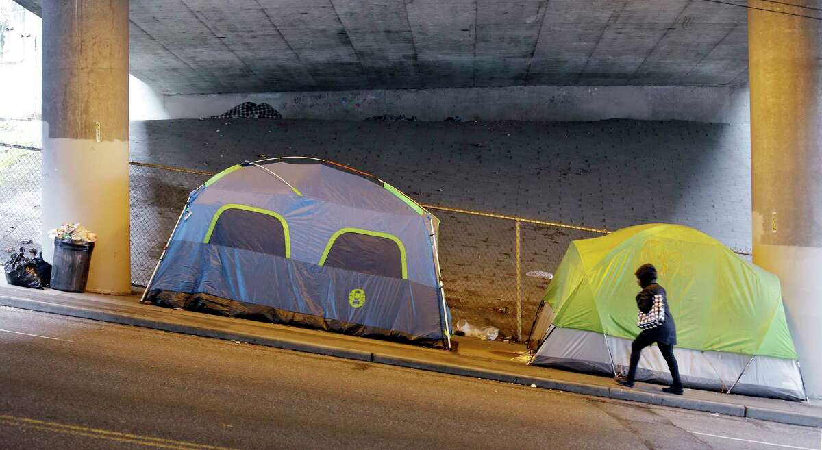 FILE - In this March 8, 2017 file photo, a person walks up a hill next to tents lined up beneath a highway and adjacent to downtown Seattle. Microsoft pledged $500 million to address homelessness and develop affordable housing in response to the Seattle region's widening affordability gap. The company plans a news conference, Thursday, Jan. 17, 2019.