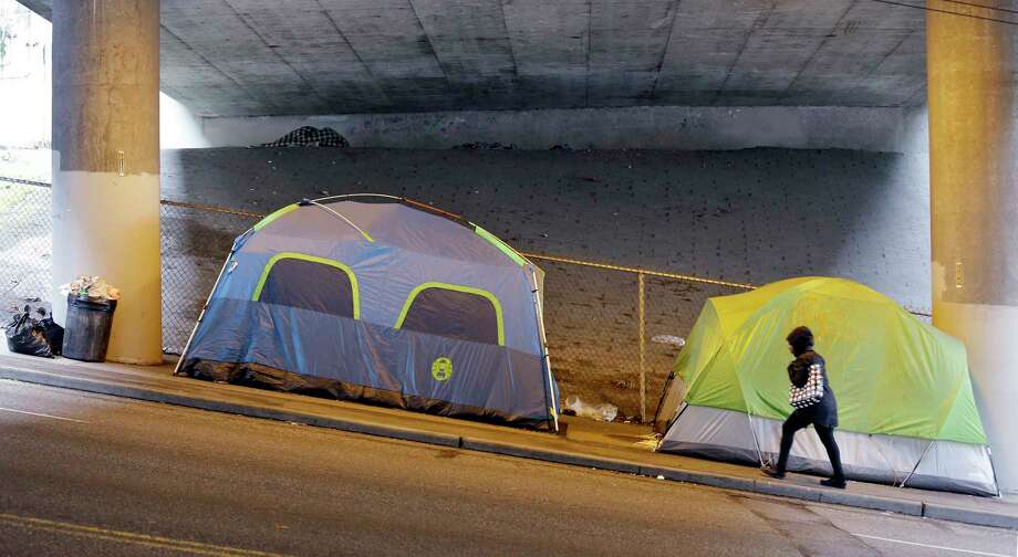 FILE - In this March 8, 2017 file photo, a person walks up a hill next to tents lined up beneath a highway and adjacent to downtown Seattle.   Microsoft pledged $500 million to address homelessness and develop affordable housing in response to the Seattle region's widening affordability gap.  The company plans a news conference, Thursday, Jan. 17, 2019. Photo: Elaine Thompson, AP / Copyright 2017 The Associated Press. All rights reserved.