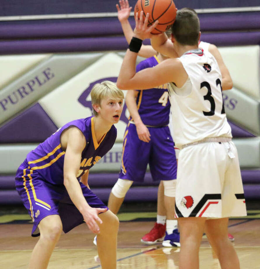 CM's Brett Lane (left) defends while Nokomis' Trevor Wright looks for a teammate during a pool game Tuesday night at Litchfield's Rick McGraw Memorial Tournment at Simmons Gym. The Eagles rebounded from a one-point loss to Nokomis to beat Mount Zion on Wednesday night at Litchfield. Photo: Greg Shashack / The Telegraph