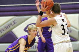 CM's Brett Lane (left) defends while Nokomis' Trevor Wright looks for a teammate during a pool game Tuesday night at Litchfield's Rick McGraw Memorial Tournment at Simmons Gym. The Eagles rebounded from a one-point loss to Nokomis to beat Mount Zion on Wednesday night at Litchfield.