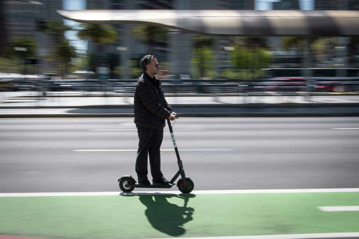 A person rides a Bird Rides shared electric scooter on the Embarcadero in San Francisco, California, on April 13, 2018.