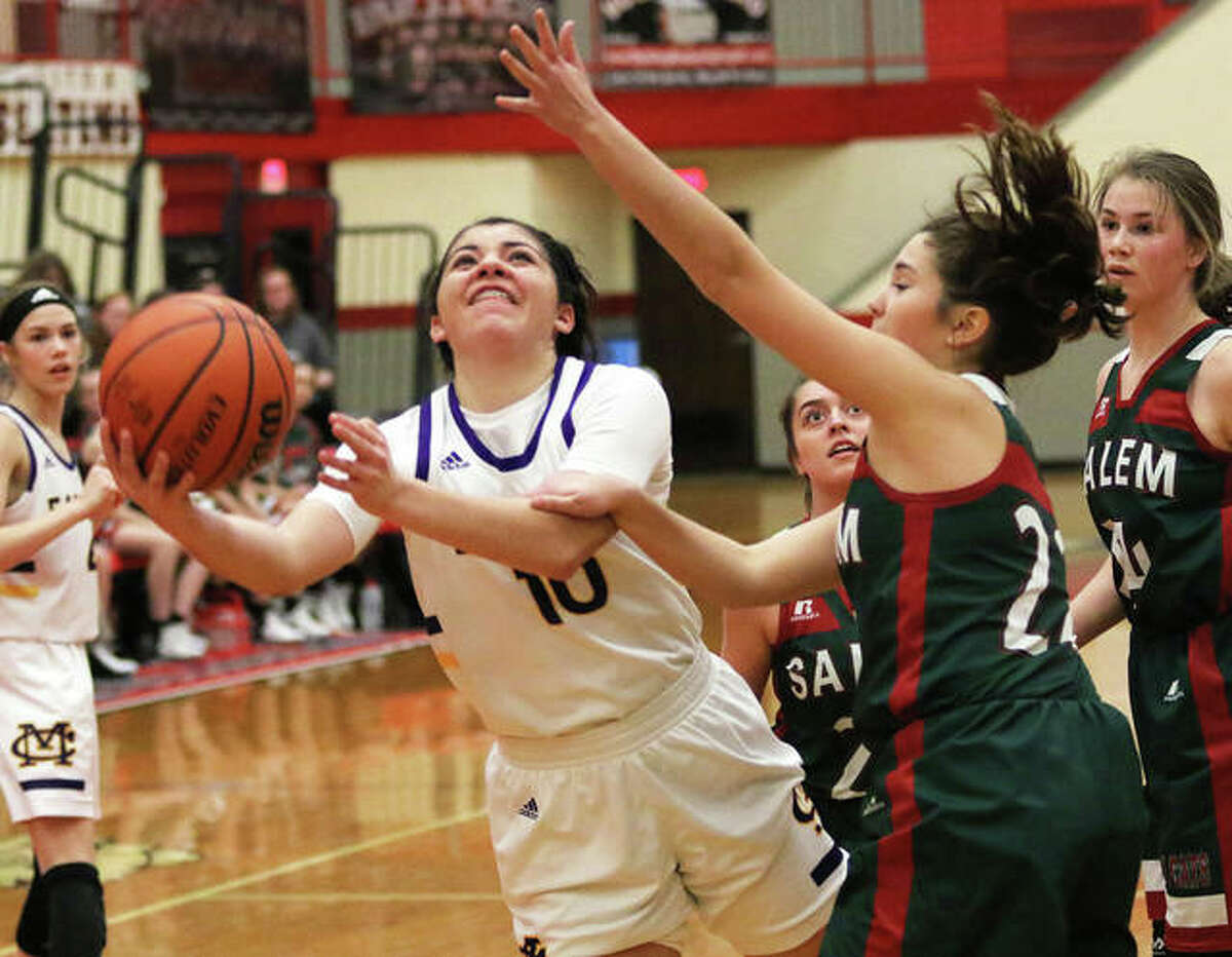 CM's Kourtland Tyus (left) ducks under Salem's Ellie Bunnell for a shot in the lane Monday at the Highland Tourney. Tyus had five assists Wednesday in the Eagles' quarterfinal victory over Nashville.